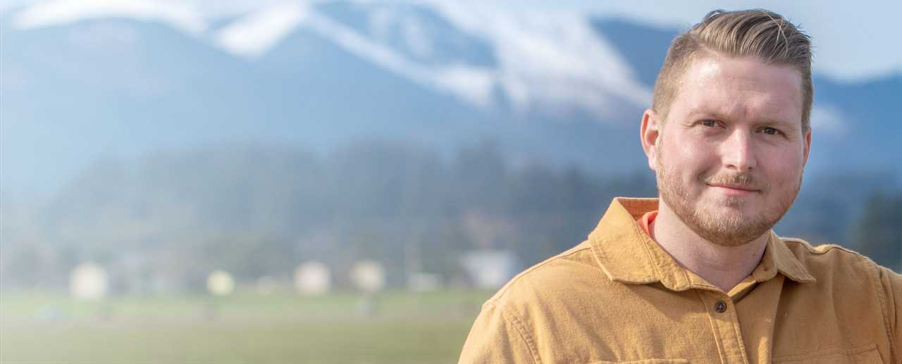 Man standing in field in front of mountains
